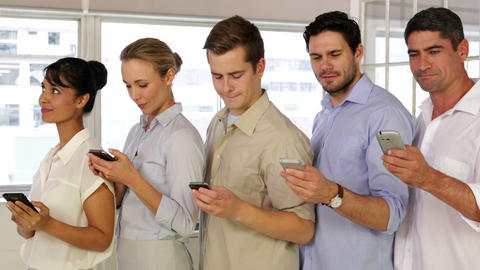 Content businesspeople text messaging while standing in a... Stock Video Footage