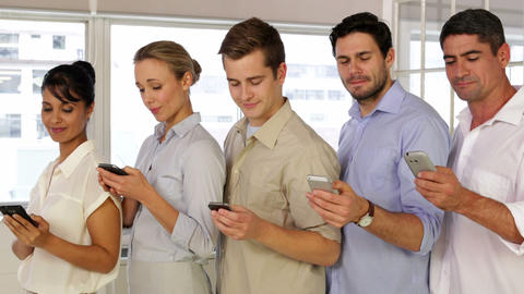 Content businesspeople text messaging while standing in a row Footage