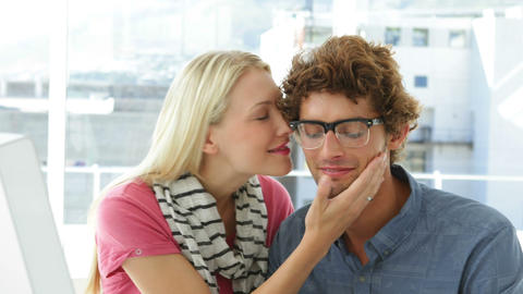 Gorgeous blonde woman kissing her colleague on his cheek Stock Video Footage