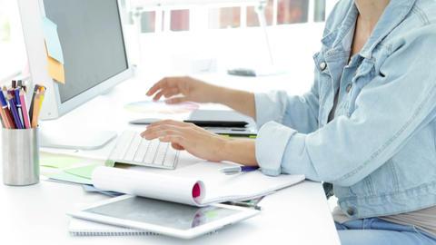 Attractive creative designer working sitting at her desk Stock Video Footage
