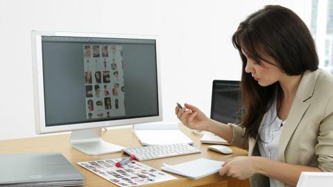 Photo editor circling photos on contact sheet Stock Video Footage