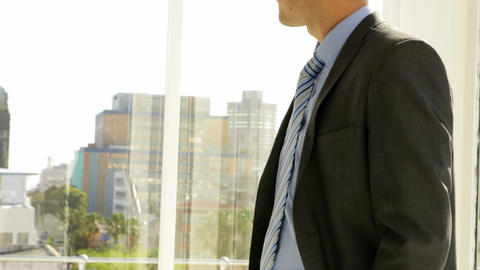 Businessman looking out his window then turning to camera Stock Video Footage