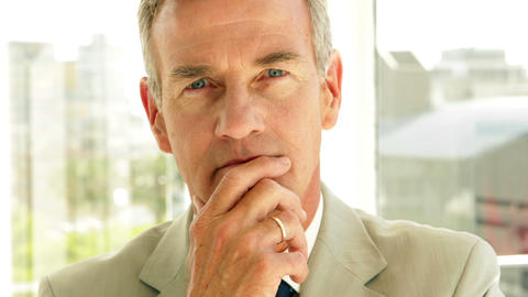Thinking businessman looking at camera Stock Video Footage