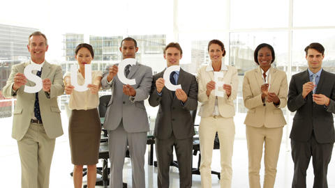 Happy business people holding letters spelling success Footage