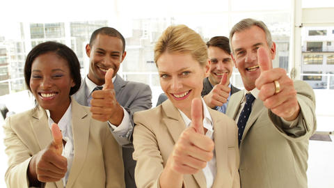 Business people giving thumbs up to camera Stock Video Footage