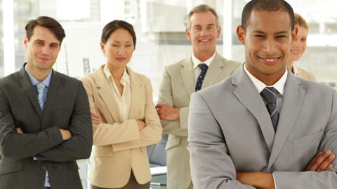 Businessman smiling at camera in front of his staff Stock Video Footage