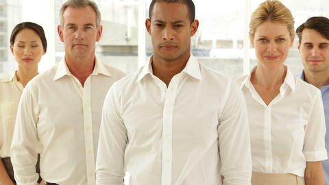 Businessman looking at camera with staff behind him Stock Video Footage