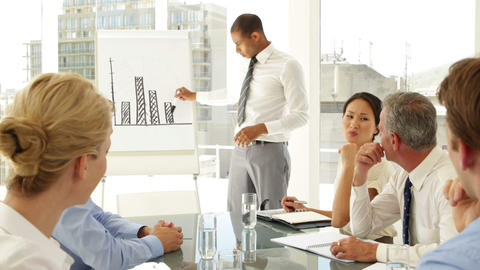 Businessman explaining bar chart to colleagues at presentation Footage