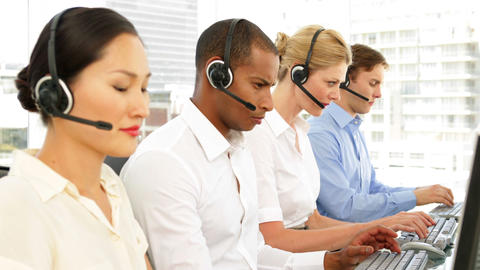 Call centre agents working with one smiling at camera Footage