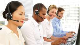 Call centre agents working with one smiling at camera Stock Video Footage