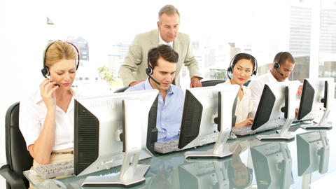 Manager checking on call centre agents Stock Video Footage