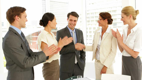 Business people shaking hands at interview while others clap Footage