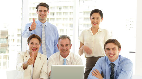 Happy business team posing in front of laptop Stock Video Footage