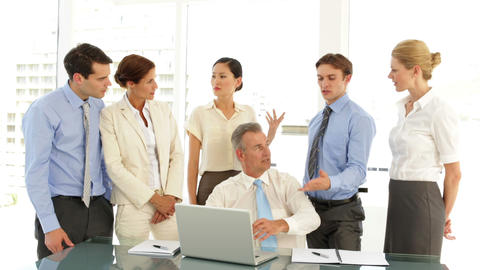 Hard working business team talking in front of laptop Stock Video Footage