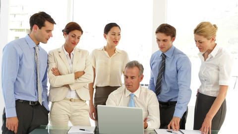 Business team talking in front of laptop then pointing to... Stock Video Footage