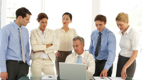 Business team in front of laptop then pointing to camera Stock Video Footage