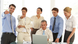 Business team in front of laptop then pointing to camera Footage