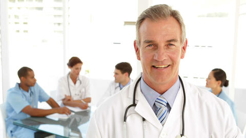 Happy doctor looking at camera and his staff behind him Stock Video Footage
