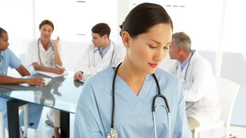 Happy nurse looking at camera with staff behind her Stock Video Footage