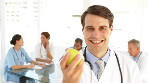 Handsome doctor holding an apple Footage