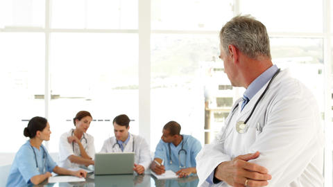 Mature doctor looking at staff and camera Footage