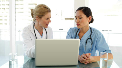 Doctor and nurse going over a file on the laptop Stock Video Footage