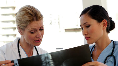 Doctor and nurse looking over xray Stock Video Footage