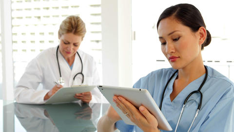 Medical workers sitting at desk using tablet Stock Video Footage