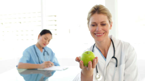 Smiling doctor showing a green apple Footage