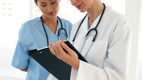 Two doctors looking over a file and looking at camera Stock Video Footage