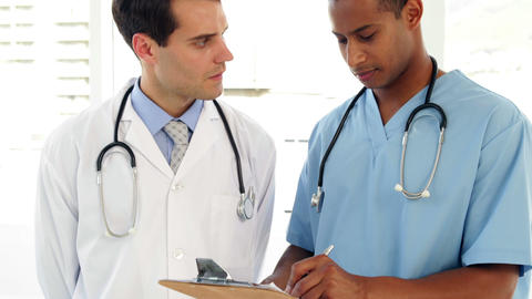 Two medical workers looking over file on clipboard Stock Video Footage