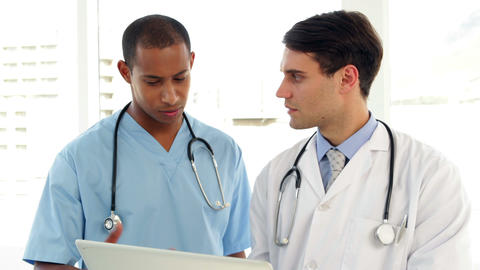 Medical workers looking over file on clipboard Stock Video Footage