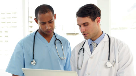 Medical workers looking over file on clipboard Footage