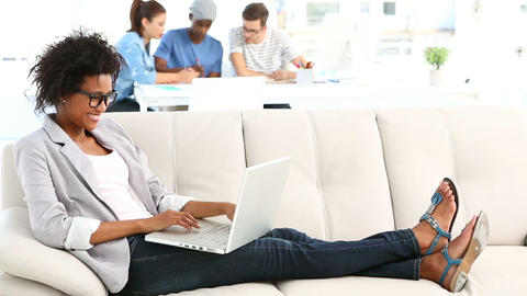 Pretty designer lying on couch working on laptop Stock Video Footage