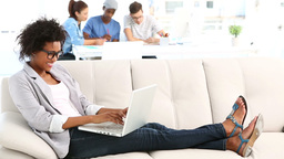 Pretty designer lying on couch working on laptop Footage