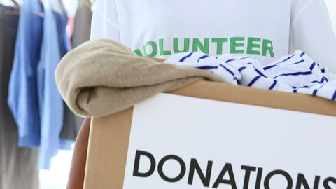 Pretty volunteer holding a clothes donation box Stock Video Footage