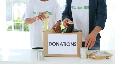 Young volunteer team packing a food donation box Stock Video Footage