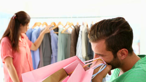 Bored boyfriend shopping with his girlfriend Stock Video Footage