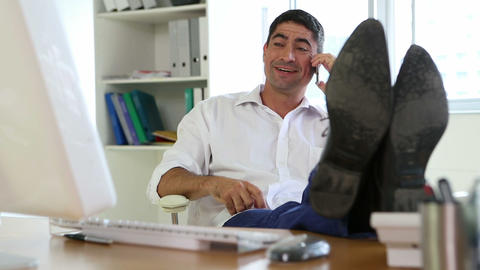 Businessman answering the phone with feet up on desk Stock Video Footage