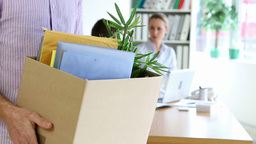Fired businessman holding box of his things Stock Video Footage