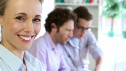 Businesswoman smiling at camera while her colleagues are... Stock Video Footage