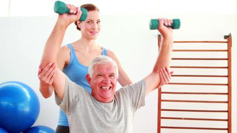 Elderly man lifting hand weights sitting on exercise ball with his trainer Footage