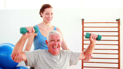 Elderly man lifting hand weights sitting on exercise ball... Stock Video Footage