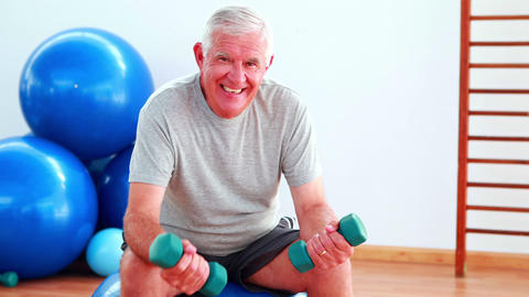 Elderly man lifting hand weights sitting on exercise ball Footage