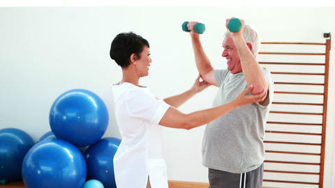 Pretty physiotherapist helping elderly patient lift hand weights Footage