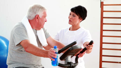 Elderly man using the exercise bike talking to... Stock Video Footage