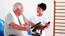 Elderly man using the exercise bike talking to physiotherapist Footage