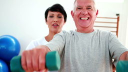Smiling physiotherapist helping elderly patient lift hand weights Footage
