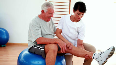 Smiling physiotherapist helping elderly patient bend knee Stock Video Footage