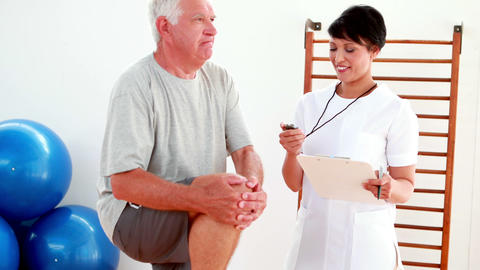 Smiling physiotherapist timing elderly patient with knee bent Footage